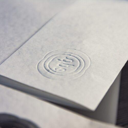 Detalle del logo impreso en golpe en seco sobre papel algodon de la papelería corporativa para la empresa EDP